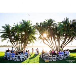 Tropical destination wedding ceremony with couple kissing guests on whitehellip
