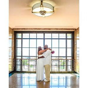Bride with magenta bouquet embracing groom with window reflections onhellip