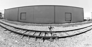 Black and white warehouse beside railroad tracks captured for ahellip