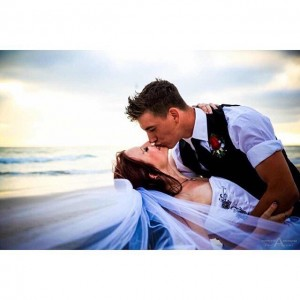 Bride with flowing veil dipped and kissed by groom withhellip