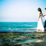 Wedding bride and groom walking on teal sea cliff in La Jolla California by Wedding Photographers Andrew Abouna