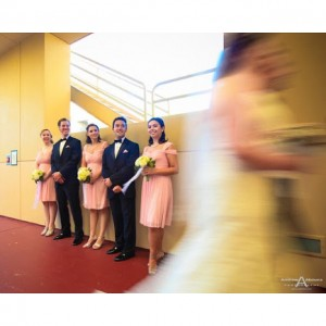 Bridesmaids in coral dresses with yellow bouquets and groomsmen withhellip