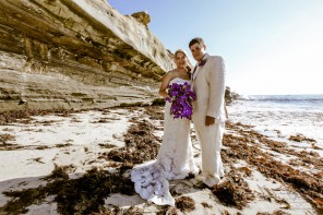 Bride and Groom on beach with purple bouquet purple corsage and sea cliff by San Diego Wedding Photographer Andrew Abouna