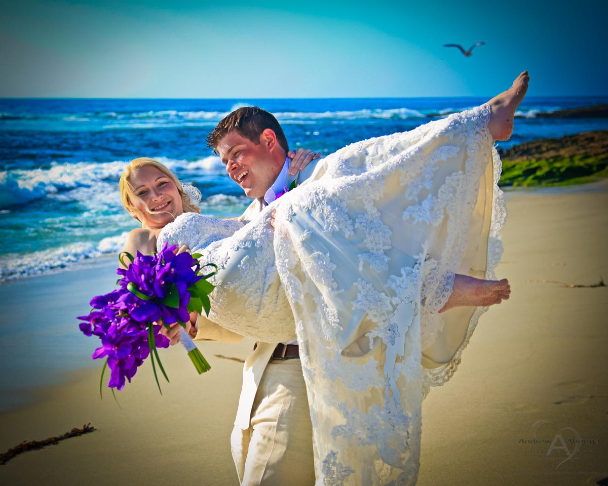 Groom Carrying Bride With Purple Wedding Bouquet Blue Ocean And
