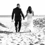Black and white wedding photo of bride and groom walking away towards ocean by Wedding Photogapher San Diego Andrew Abouna