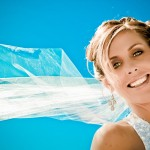 Blonde bride with updo wedding hair style with wedding veil blowing in wind and blue sky by Wedding Photographers Andrew Abouna