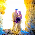 Bride and Groom in back lit sea cave with purple bouquet by San Diego Wedding Photographer Andrew Abouna