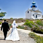 Bride and groom walking towards light house_her white wedding dress with short sleeves and veil by San Diego Wedding Photographers Andrew Abouna-