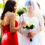Bride with bouquet and bridesmaid in red with bouquet by AbounaPhoto