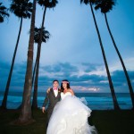 Bride with princess wedding dress magenta flower hairpiece groom in gray suit magenta bowtie with tall California Palms and ocean by La Jolla Wedding Photographer Andrew Abouna