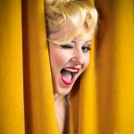Girl Ashland with blonde hairstyle with long bangs red lipstick and winking with fun smile peaking through yellow stage curtains by San Diego Photographer Andrew Abouna-9464