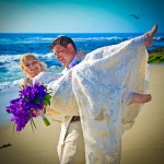 Groom carrying bride with purple wedding bouquet blue ocean and birds flying by San Diego Wedding Photographer Andrew Abouna