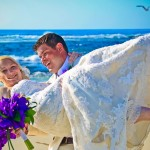 Groom holding bride on sandy beach by San Diego Wedding Photographer Andrew Abouna-