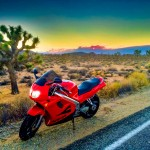 Honda VFR 750 with lights on in Joshua Tree National Park near Palm Springs California with sunset behind smoke of forest fire in the distance by San Diego Photographer Andrew Abouna-