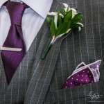 Mens boutonniere with purple pocket handkerchief and purple necktie with gray and white pinstripe suit jacket by Wedding Photographer San Diego Andrew Abouna-