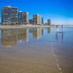 Newlyweds walking on beach reflection by San Diego Wedding Photographer Andrew Abouna-