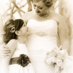 Nostalgic bride with updo hairstyle and hair net and wedding dress belt with flower girl in dress with black belt by Wedding Photographers Andrew Abouna