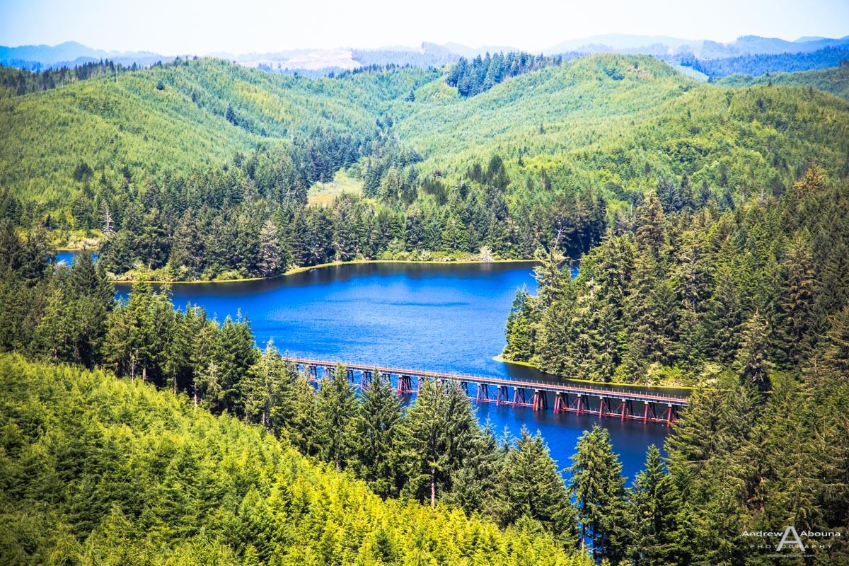 Railroad bridge across Oregon lake with pine tree hills by ...