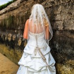 Ruffle wedding dress with back lace up and wedding veil on blonde hair bride near sea wall by Wedding Photogapher San Diego Andrew Abouna