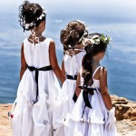 Three flower girls each in a white dress with black sash looking towards the ocean by San Diego Wedding Photographers Andrew Abouna-