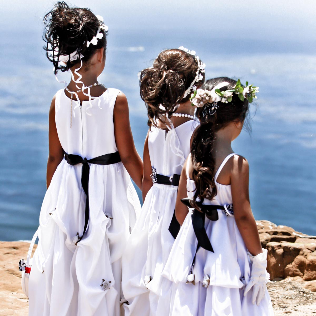 Three Flower Girls Each In A White Dress With Black Sash Looking