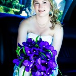 Wedding bouquet with purple orchids and bride with updo curls hairstyle small hair net semi sweetheart wedding dress in limo by Wedding Photographers San Diego Andrew Abouna-1