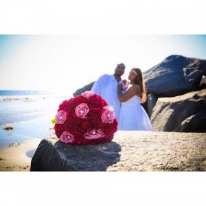Magenta wedding bouquet in the foreground with bride and groomhellip