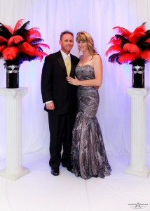 Posed Onsite Event and Portrait Background Ideas - white pleated background with uplighting and red and black feather bouquets on pedestals with couple - AbounaPhoto--7