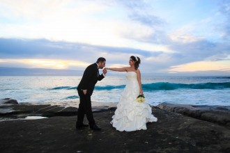 Groom in tux kisses hand of bride in wedding dress on rocky beach with ocean waves at sunset by wedding photographers in San Diego AbounaPhoto