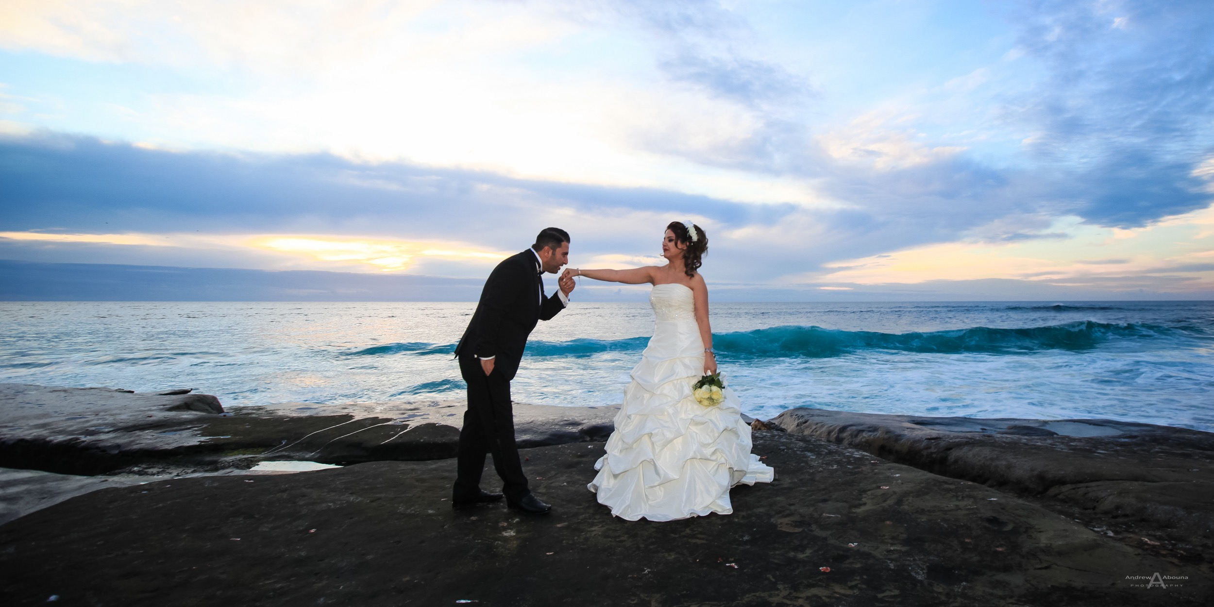 Groom in tux kisses hand of bride in wedding dress on rocky beach ...