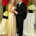 posed-onsite-event-and-portrait-background-ideas-hand-painted-backdrop-with-red-gladiola-bouquets-on-draped-pedestals-with-couple-abounaphoto-8-414x580
