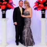 posed-onsite-event-and-portrait-background-ideas-white-pleated-background-with-uplighting-and-red-and-black-feather-bouquets-on-pedestals-with-couple-abounaphoto-7-414x580